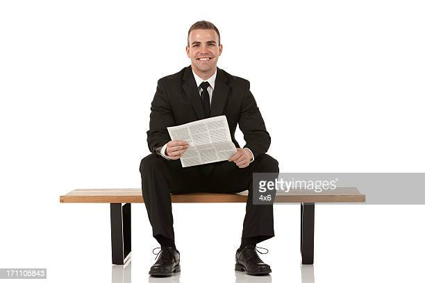 Businessman sitting on bench and holding a newspaper