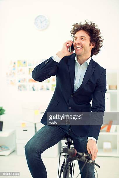 Businessman sitting on bicycle in the office.