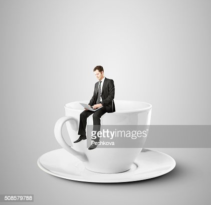 businessman sitting on coffee cup : Stock Photo