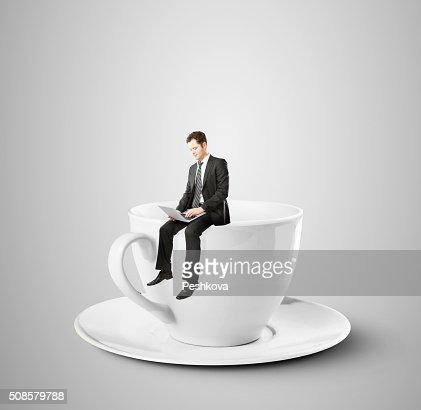 コーヒーカップに座っているビジネスマン : ストックフォト