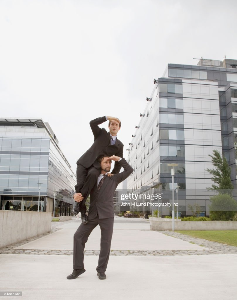 Businessman sitting on co-worker?s shoulder looking : Stock Photo