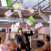 Businessman sitting on desk throwing papers