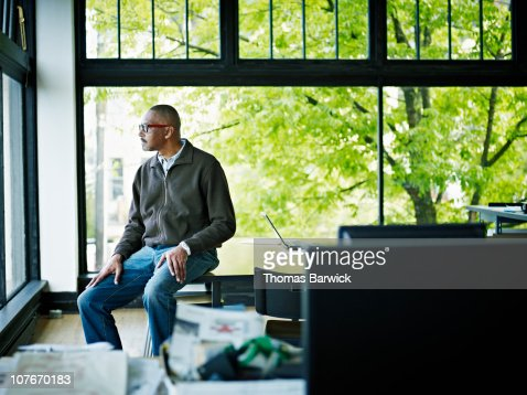 Businessman sitting on edge of table looking out : Stock Photo