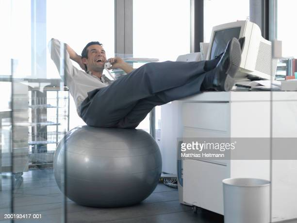 Businessman sitting on excercise ball at desk, using phone, laughing