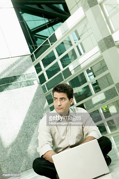 Businessman sitting on floor and working on laptop and looking up, tilt
