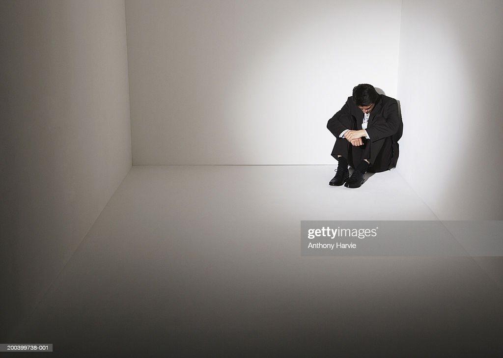 Businessman sitting on floor in corner of room : Stock Photo