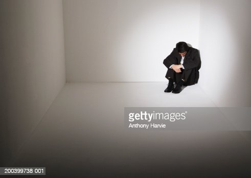 Businessman sitting on floor in corner of room : Bildbanksbilder