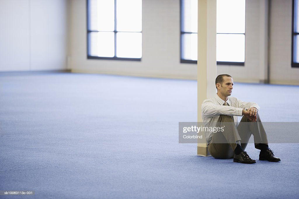 Businessman sitting on floor in empty office : Stock Photo