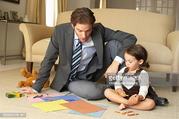 Businessman sitting on floor looking at daughter's (2-4) drawings