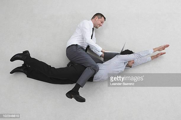 Businessman sitting on flying man's back, using laptop