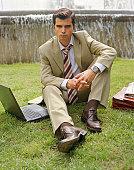 Businessman sitting on grass by laptop, portrait
