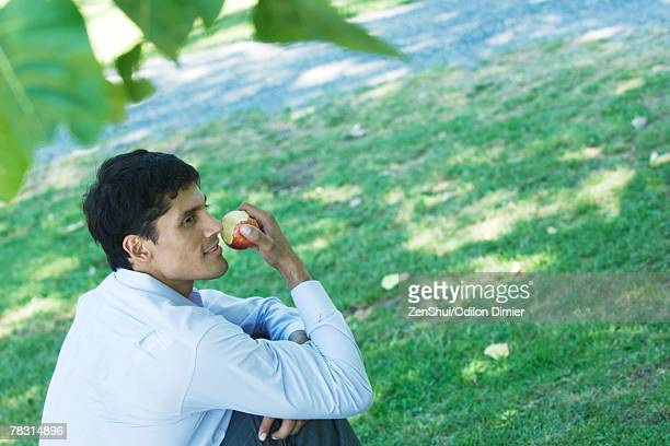 Businessman sitting on ground in park, eating apple