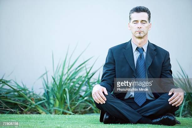 Businessman sitting on ground outdoors, meditating, eyes closed