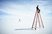 Businessman sitting on large ladder in lake