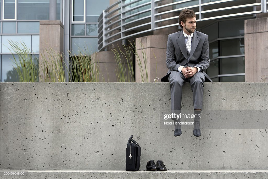 Businessman sitting on ledge with shoes and briefcase : Stock Photo
