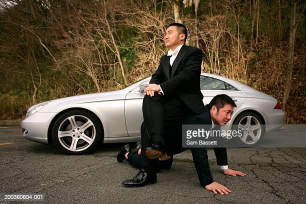 Businessman sitting on man's back near car