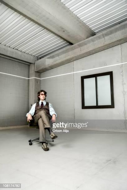 Homme d'affaires assis sur une chaise dans la salle vide
