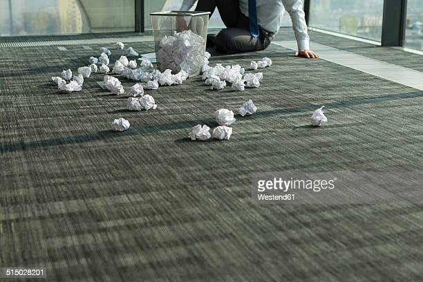 Businessman sitting on office floor surrounded by crumpled paper