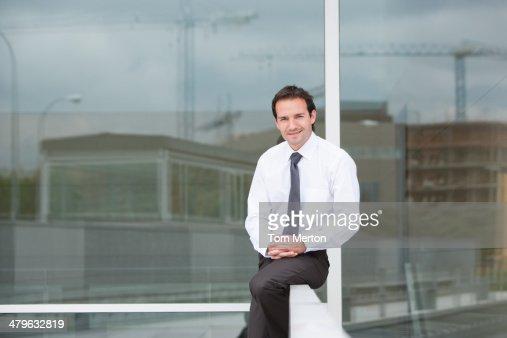 Businessman sitting on railing : Stock Photo