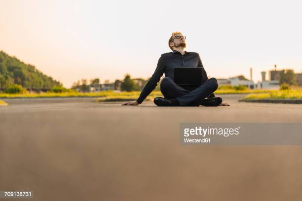Businessman sitting on rural road with laptop