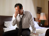 Businessman sitting on side of bed, looking tired.