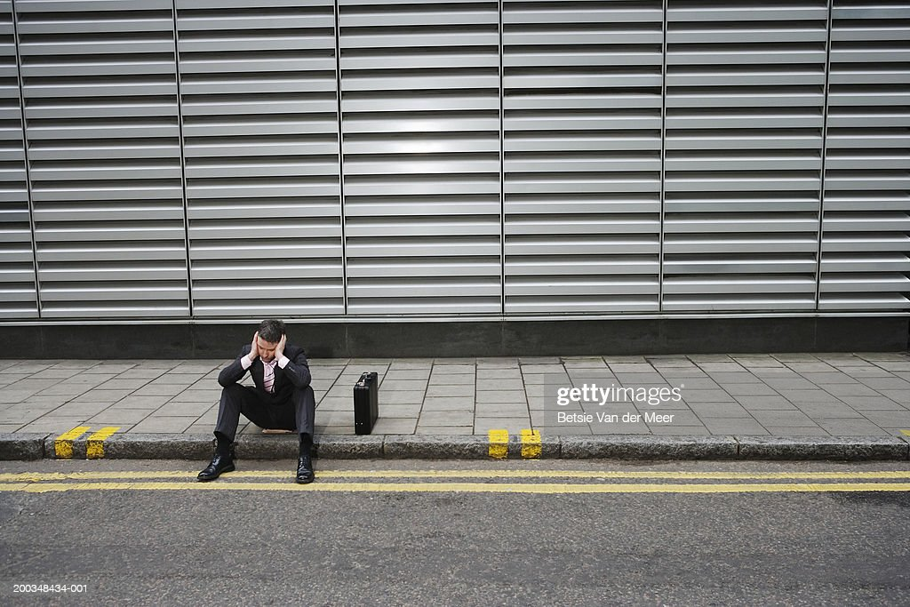 Businessman sitting on side of road by briefcase