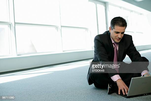 Businessman sitting on the floor working with a laptop