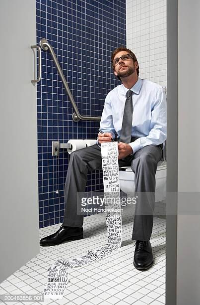 Ejecutivo sentado en el sanitario escrito lista en papel