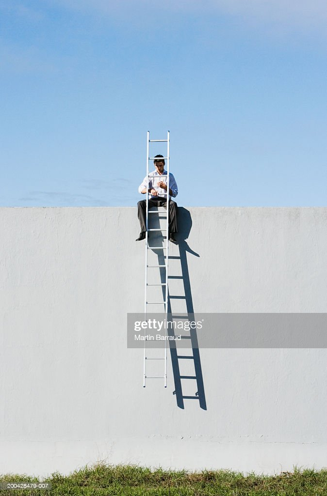 Businessman sitting on wall lifting ladder away from ground : Stock Photo