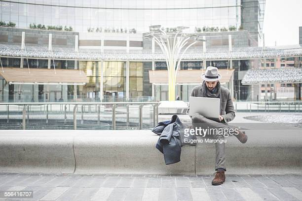 Businessman sitting on wall using laptop