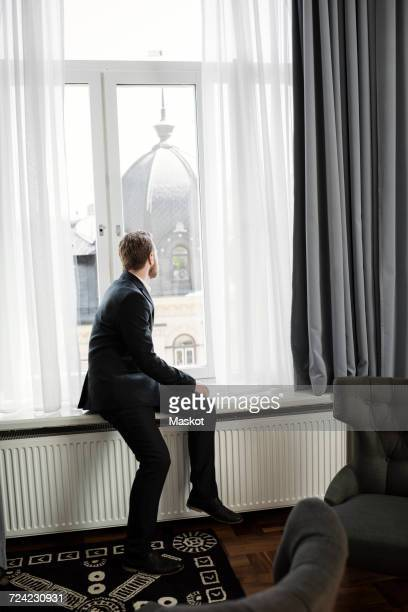 Businessman sitting on window sill looking at dome in hotel room