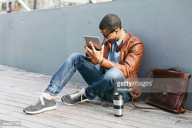 Businessman sitting on wooden floor using mini tablet