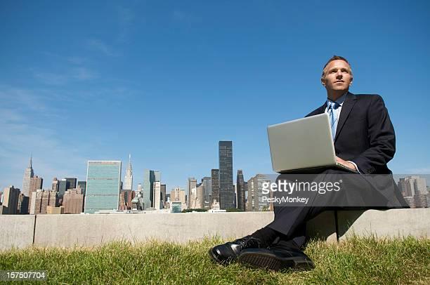 Geschäftsmann, Sitzen im Freien mit Laptop vor Skyline