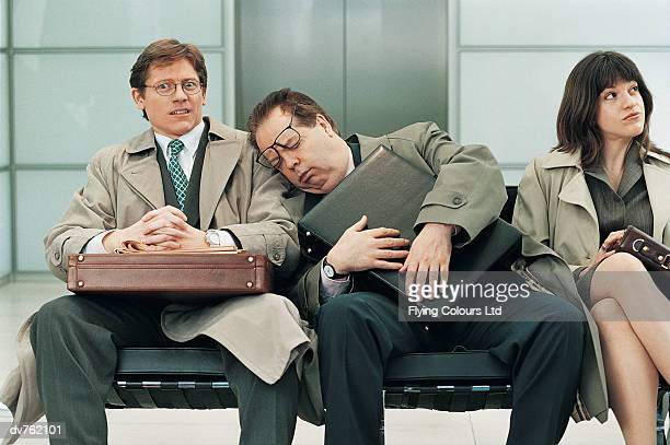 Businessman Sitting Sleeping With His Head on Another Businessman's Shoulder