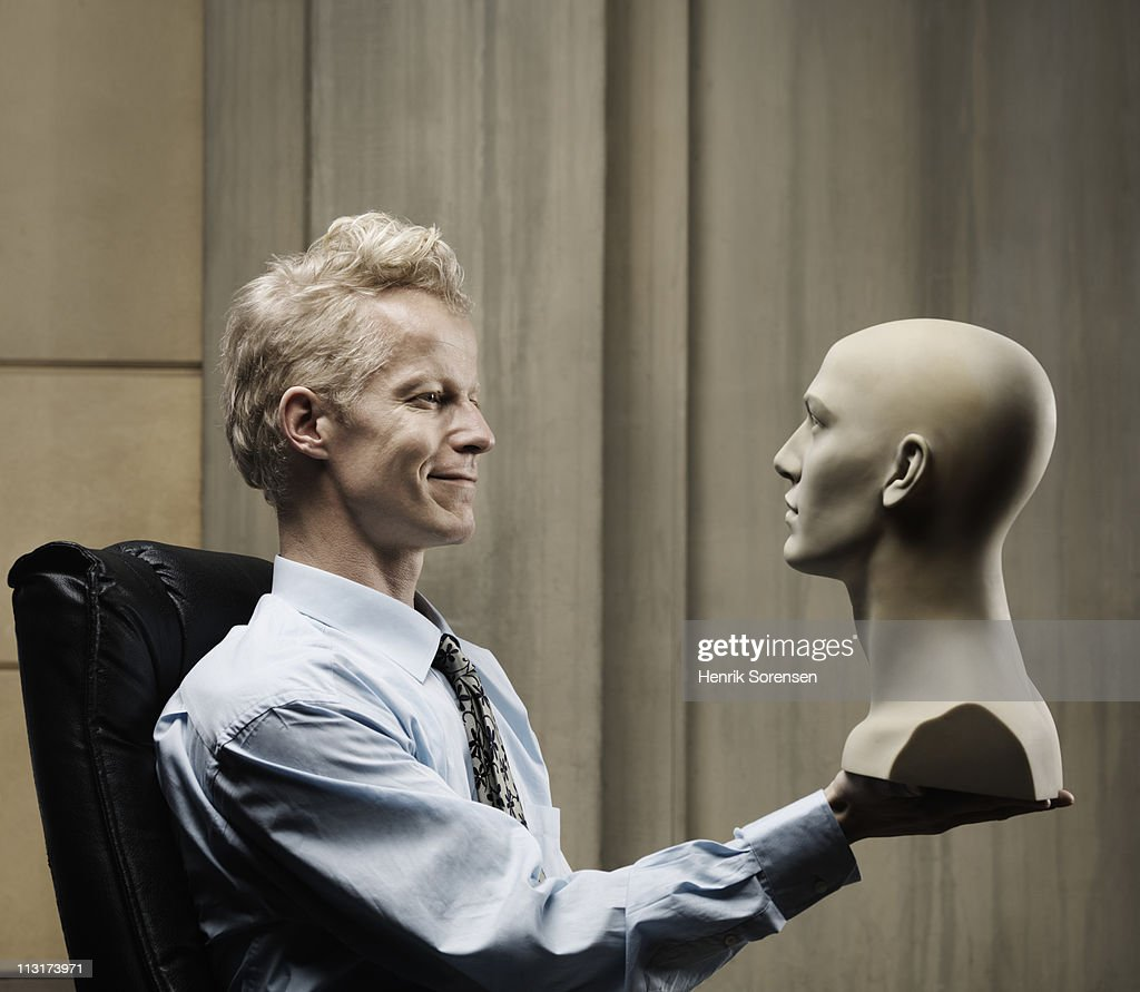 Businessman sitting with bust in hand : Stock Photo