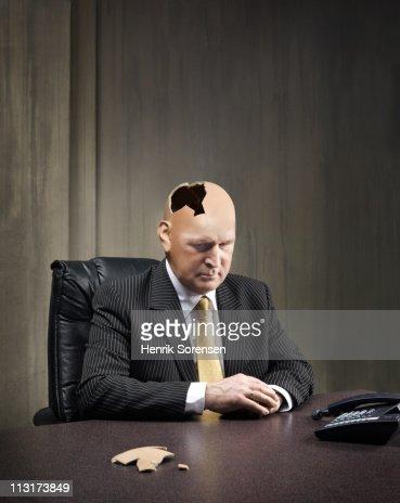 Businessman sitting with damaged head : Stock Photo