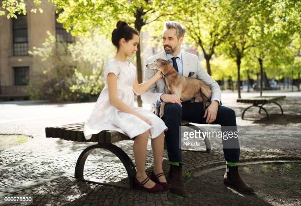 Businessman sitting with daughter and dog on bench at park