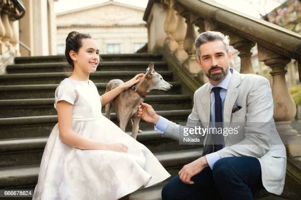 Businessman sitting with daughter and dog on steps in city