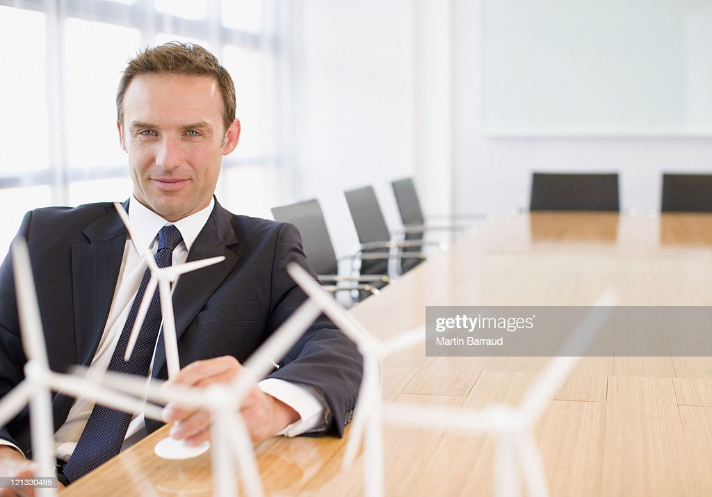 Businessman sitting with model wind turbines in conference room : Stock Photo