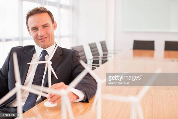 座っているビジネスマン、モデルの風力タービンのコンファレンスルーム