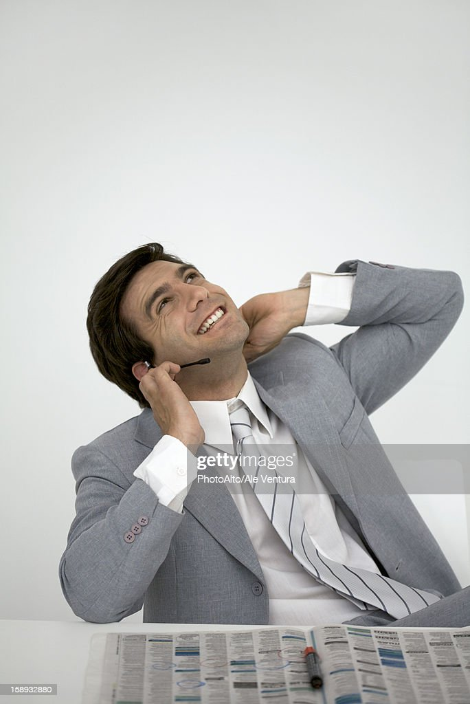 Businessman sitting with newspaper, talking on headset : Stock Photo