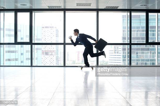 Businessman skateboarding with cup and briefcase in hands