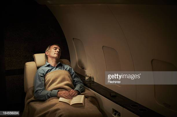 Businessman sleeping aboard private jet