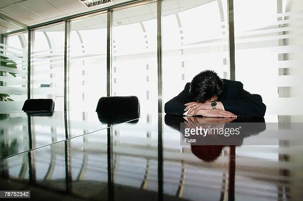 Businessman Sleeping at Conference Table
