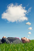 Businessman Lies Dreaming with Thought Bubble Clouds