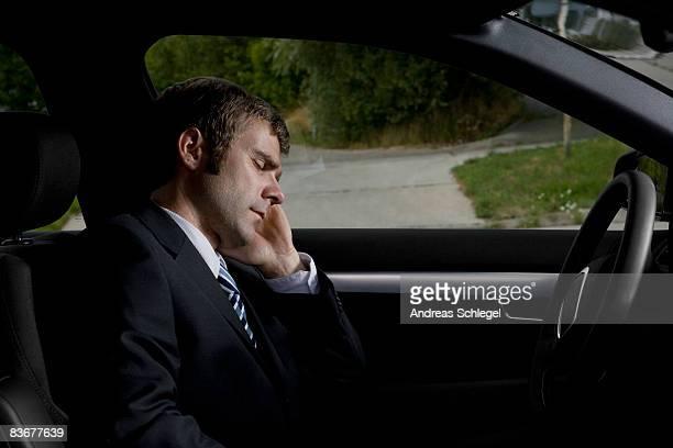 A businessman sleeping in a car