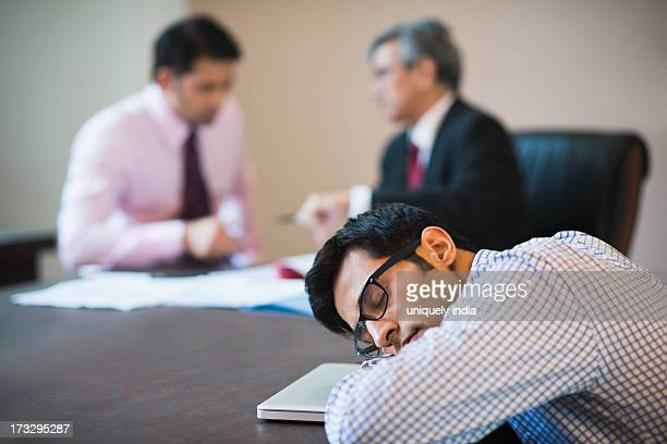 Businessman sleeping in a conference with two businessmen in the background