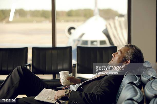 Businessman sleeping in airport concourse