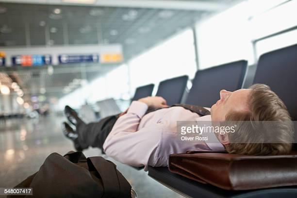 Businessman sleeping in airport terminal