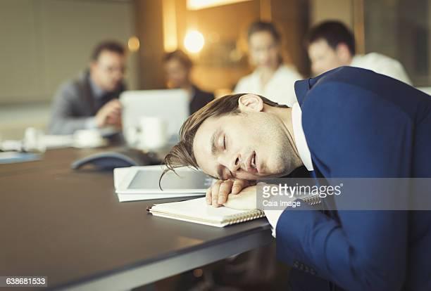 Businessman sleeping in conference room meeting